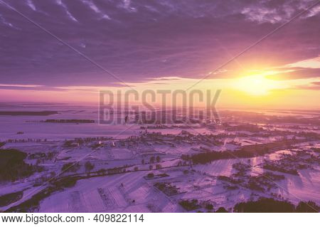 Panoramic Fantastic View From Above Of Coutryside Covered With Snow In Winter During Beautiful Sunse