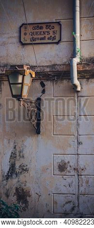 Steel Street Lamp And Queen's Street Sign In A Rusty Wall Galle Fort. Evening Light Brighten Up The