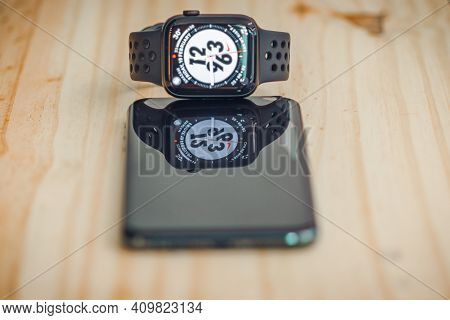 Apple I Watch Series 6 And Iphone 11 Pro Max Lay Flat In A Wooden Table, Watch's Display Analog Cloc