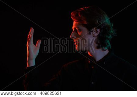 Dark portrait of a handsome young man with wavy blond hair looking at the palm of his hand in black background background in red light. Side view. Men's beauty.