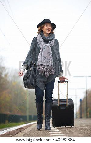 Smiling Woman Walking On Train Station Platform