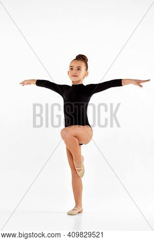 Adorable Gymnast Child Girl In Black Sportswear Performs Gymnastic Exercises