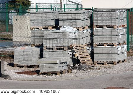 Grey Stone Tiles And Concrete Curbs Stacked On Top Of Wooden Pallets At Local Construction Site Surr