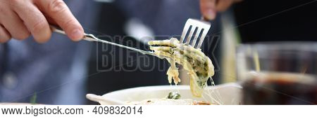 Bistro Visitor Sitting At Table Holding Fork And Knife With Piece Of Bolognese. Lunch Menu In Restau