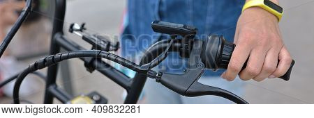 Man Holds Handlebars Of Black Bicycle In Street. Cycling For Health And As A Lifestyle Concept