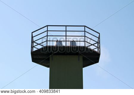 Two Shiny Metal Industrial Chimney Tops Surrounded With Metal Fence And Safety Platform Rising High