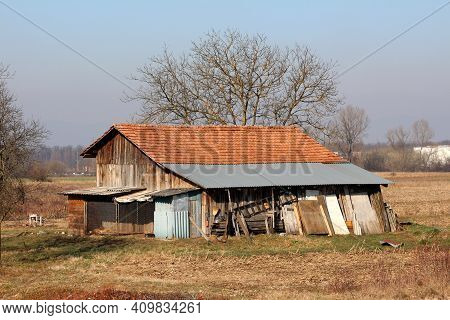Wooden Boards Old Barn With Attached Storage Shed And Improvised Dog Kennel Surrounded With Dry Gras