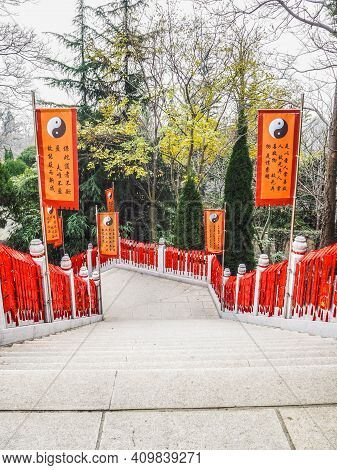 Qingdao, China - December 2017: Stairs Hanging Full With Red Whishing Cards And Flanked By Orange Ta