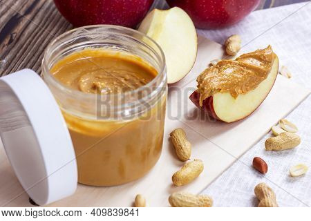 Fresh Homemade Crunchy Peanut Butter With Nuts And Apples On Light Wooden Background In The Kitchen.