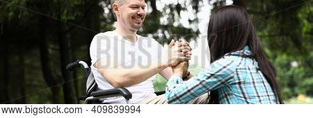 Disabled Man In Love Sit In Wheelchair And Hold Woman Hands In Park.