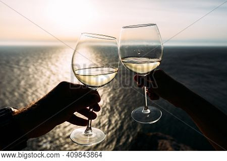 Hand Holding Glass Of Wine Over The Sea. Chin-chin. Romantic Vacation. Two Hands Holding Wine Glasse
