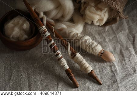 Soft White Wool And Spindles On Table
