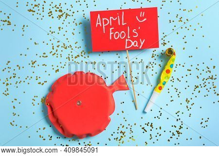 Sign With Phrase April Fools' Day, Whoopee Cushion And Party Blower On Light Blue Background, Flat L