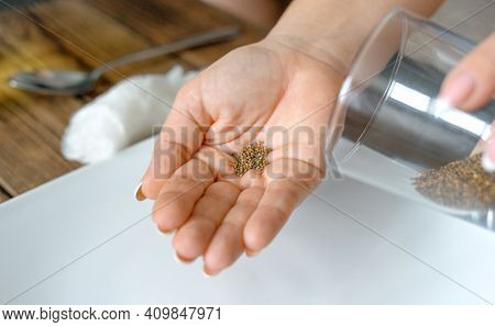 Home Gardening. Woman Poured Arugula Seeds From A Glass Into Her Palm. Preparation For Planting Arug
