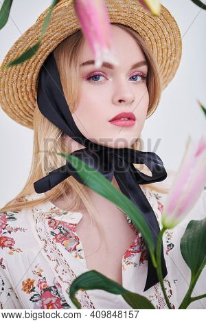 Beautiful blonde girl in a summer blouse poses with lily flowers on a white background. Light fresh makeup in pink colors. Inspiration of spring and summer.