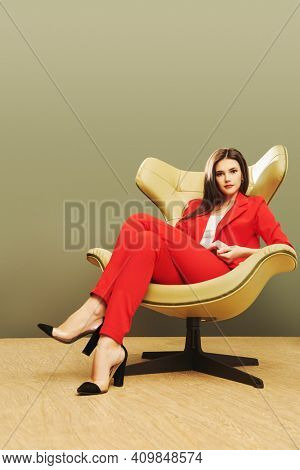 Full length portrait of a beautiful business lady sitting in a chair in Art Nouveau style. Business, elegant businesswoman. Interior, furniture. Copy space.