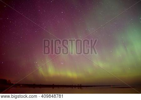 intense northern lights aurora borealis over beach in Latvia