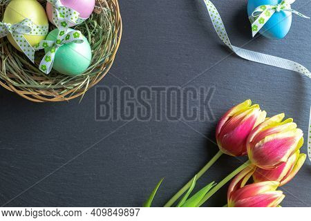 Easter Bunny. Colourful Egg With Tape Ribbon, Spring Tulips On Dark Rough Stone Background In Happy