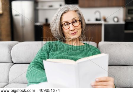 Intelligent Elderly Woman Is Reading A Book Sitting On The Sofa At Home. Well Looking Mature Lady Sp