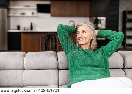 The Winsome Senior Lady Is Resting On The Comfortable Couch At Home, Charming Elderly Woman In Casua