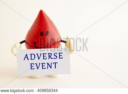 A Toy Drop Of Blood Holds A White Paper Card With The Inscription Adverse Event. Medical Concept.