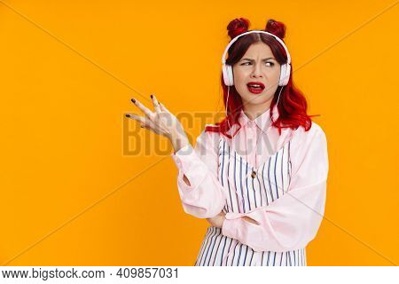 Perplexed girl with red hair gesturing while listening music with headphones isolated over yellow background