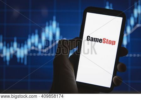 London, Uk - February 2021: Gamestop Logo In Front Of Stock Market Price Graph