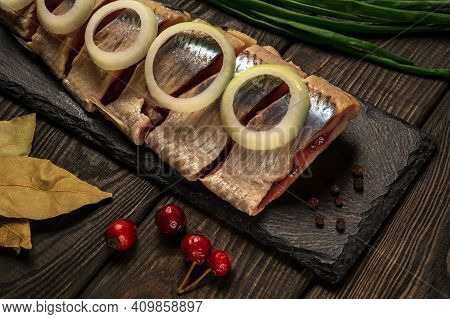 Raw Norwegian Herring With Onions And Spices On A Serving Board Close-up. The Idea Of A Snack For St