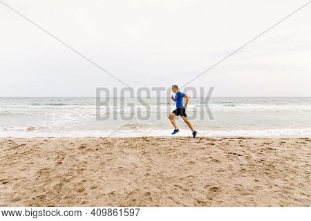 Male Jogger Run Sandy Beach In Background Of Sea And Sky