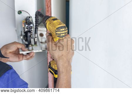 The Hands Of A Mechanic Holding A Automatic Screwdriver To Fix The Vending Machine.