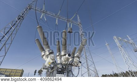 City Electric Transformer Above The Ground Against Blue Sky. Action. Bottom View Of A Transformer At