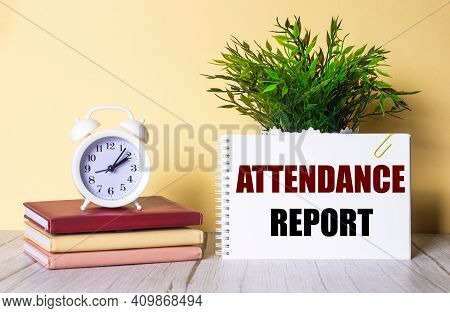 Attendance Report Is Written In A Notebook Next To A Green Plant And A White Alarm Clock, Which Stan