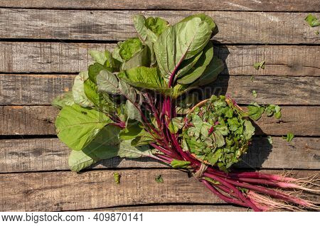 Amaranthus Dubius Or Red Spinach Leafy Vegetable Isolated On Wooden Background
