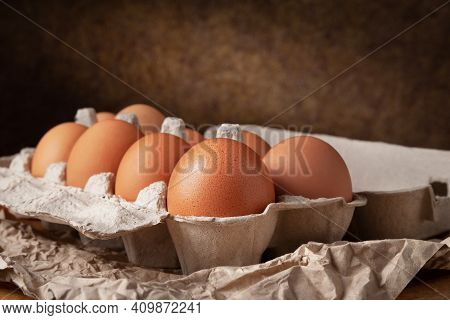 Chicken Eggs In An Egg Box. Raw Brown Chicken Eggs On Crumpled Wrapping Paper On A Dark Background.