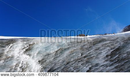 High Ice Wall In The Mountains. The Bogdanovich Glacier. The Black-and-white Ice Mixed. Grains Of Sn