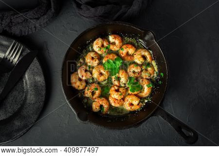 Shrimps with garlic, olive oil and parsley in frypan on black background