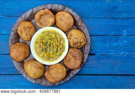 Khasta Kachori With Curried Yellow Peas Or Ghugni Curry In A Leaf Plate Isolated  Blue Wooden Backgr