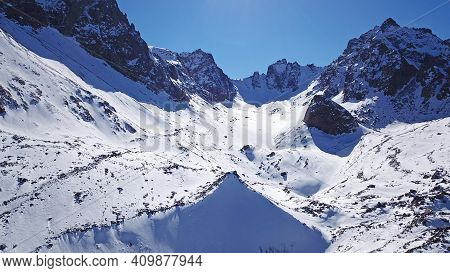 High Snow-capped Peaks And Glaciers. Top View From The Drone. Steep Cliffs, The Wind Blows Away The
