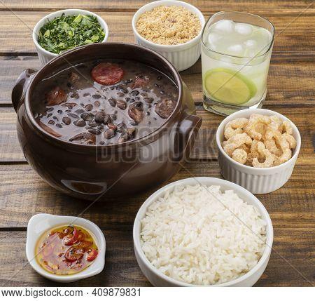 Traditional Brazilian Feijoada With Kale, Rice, Cracklings, Manioc Flour And Caipirinha.