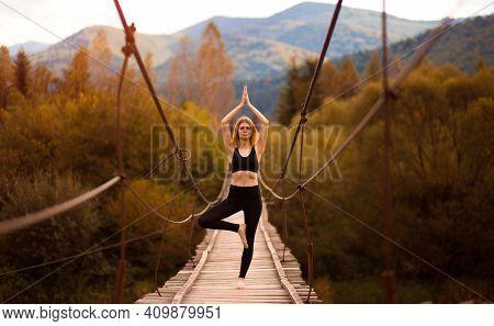 Yoga Outdoor. Young Woman Do Yoga Balance Exercises. Yoga Meditation On Bridge Over River With Mount