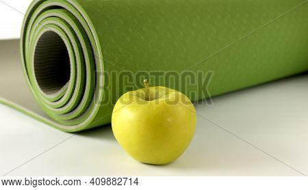Yoga Fitness, Health Life Style. Yoga Rolled Green Mat And Green Apple On White Background. Place Fo