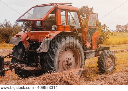 Old Red Tractor In The Field During The Haymaking Season, Pressing Hay On Bales, Forage Harvesting.