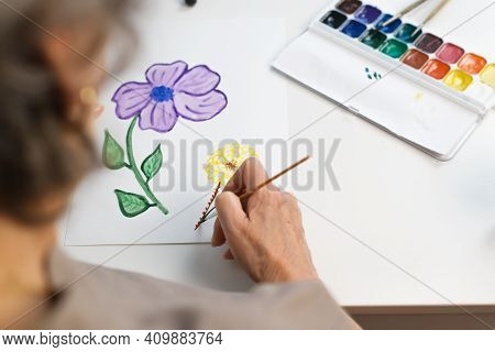 Elderly Woman Painting Flower With Watercolors At Home. Female Hands Holding A Paintbrush, Paper And
