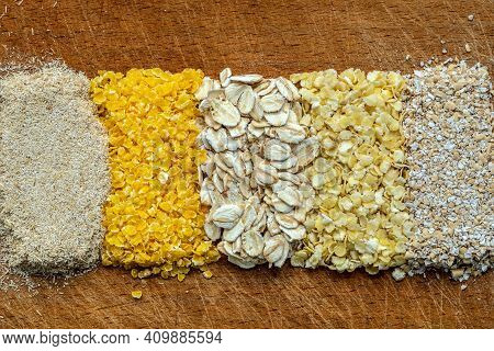 Oat Flakes, Corn Flakes, Millet Flakes And Two Types Of Oat Bran On A Wooden Board.