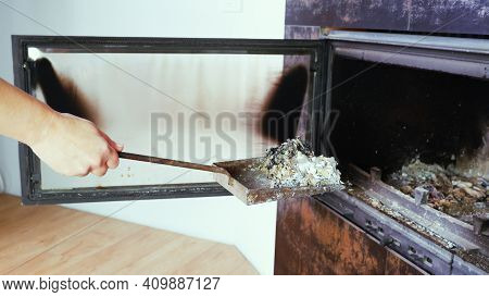 Fireplace Cleaning. Woman Hand Holds A Shovel With Ash.a Hand Collects Ash From The Fireplace On An