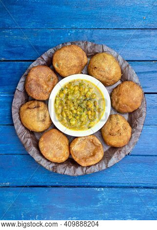 Top View Of Khasta Kachori With Curried Yellow Peas Or Ghugni Curry In A Leaf Plate Isolated  Blue W