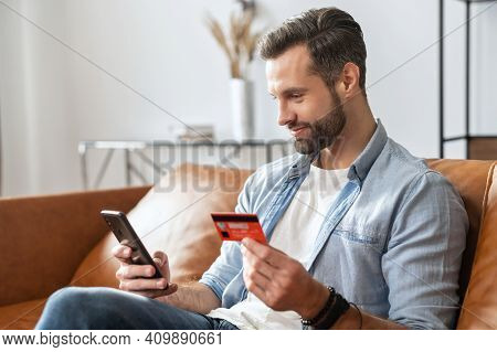 Bearded Hipster Guy Businessman, Holding Mobile Phone And Credit Card For Online Shopping And Enteri