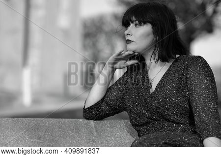 Portrait Of A Beautiful Young Parisian Woman Sitting On A Bench In Paris France