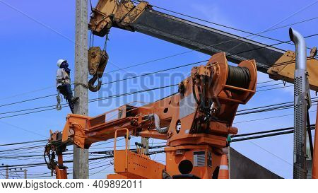 Electrical Worker With Crane Truck Working To Install Electric Power Pole On Roadside Against Blue S