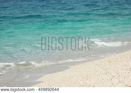 Clear Turquoise Sea Water On White Sandy Beach. Close Up Of Sandy Beach With Crystal Clear Water. Se